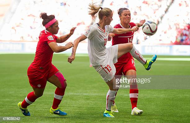 AnaMaria Crnogorcevic of Switzerland tries to control the ball while being challenged by Josee Belanger and Melissa Tancredi of Canada during the...