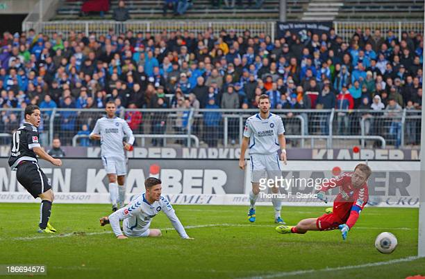 Anass Achahbar of Bielefeld scores his teams first goal against Dennis Kempe and goalkeeper Dirk Orlishausen of Karlsruhe during the Second...