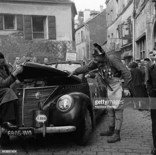 Anatole le garde champêtre examinant une voiture lors de la course de lenteur à Montmartre à Paris France en 1954