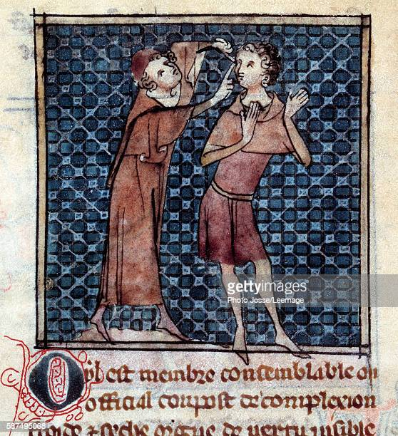 doctor examining a patient's eye Miniature from the manuscript 'Surgery' written by Henri de Mondeville 14th century BN Paris France
