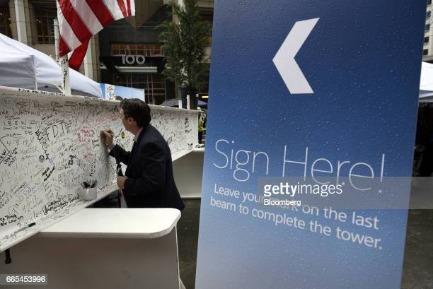 Anattendee signs the final steel beam during a topping off ceremony for the Salesforce Tower in San Francisco California US on Thursday April 6 2017...