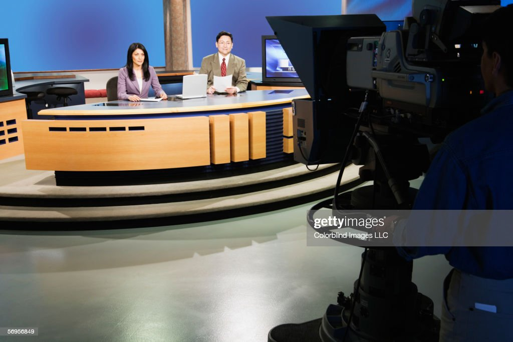 Anchor people on set in TV newsroom : Stock Photo