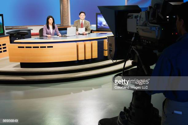 Anchor people on set in TV newsroom