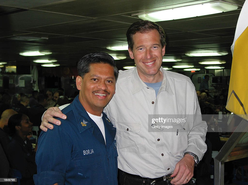NBC anchorman Brian Williams poses with Dental Technician 1st Class Ervin Borja aboard the amphibious assault ship USS Tarawa March 13 2003 at sea in...