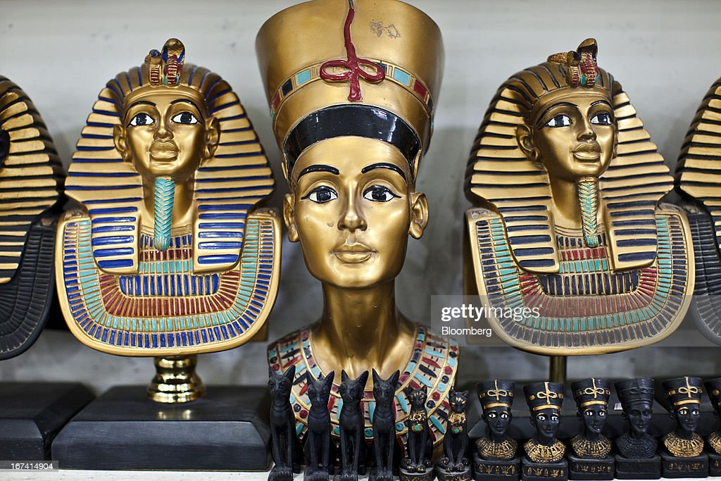 Ancient Egyptian-themed souvenirs including a bust of Nefertiti, center, and Tutankhamun death masks stand on display inside a tourist store in Luxor, Egypt, on Wednesday, April 24, 2013. Egypt ranked last in terms of security and safety on the World Economic Forum's 2013 Travel and Tourism Competitiveness Index. Photographer: Shawn Baldwin/Bloomberg via Getty Images