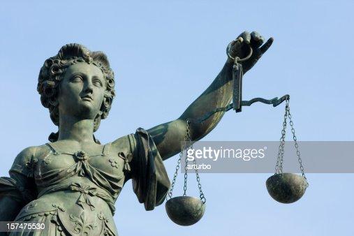 ancient Lady Justice statue half portrait against blue sky