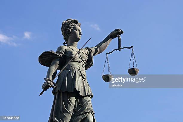 ancient Lady Justice statue with scale and sword