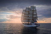 Ancient sailing ship in the sea at sunset