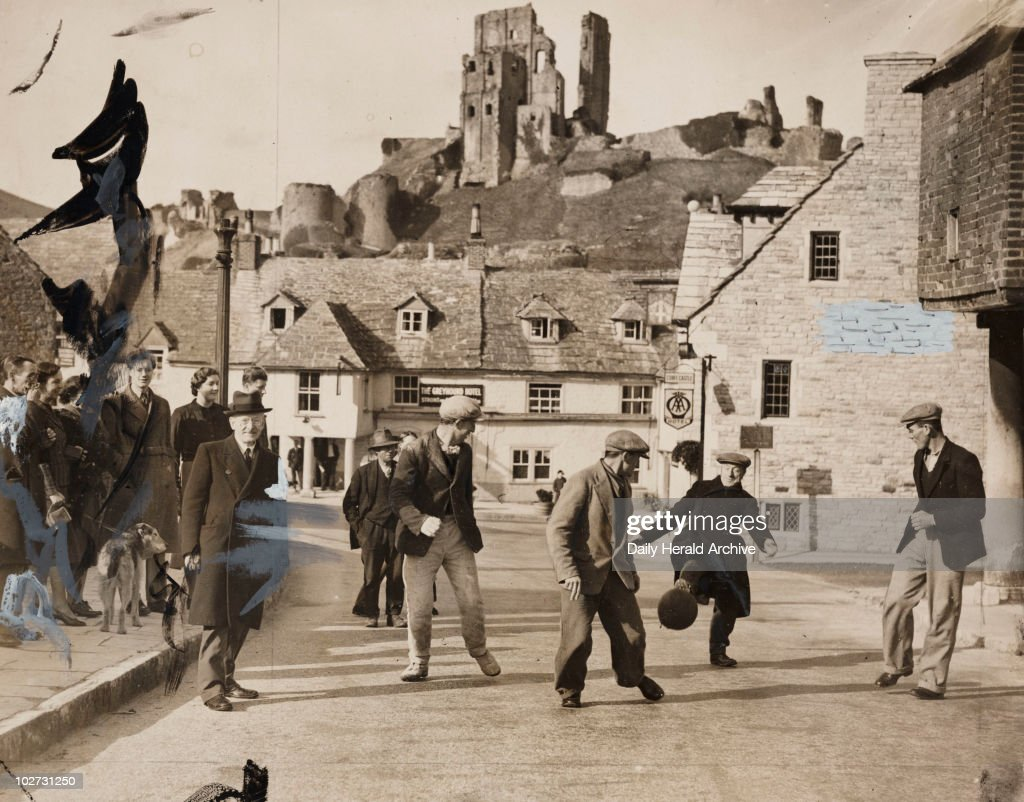 'Ancient Shrove Tuesday Custom Observed in Dorset', 1939. A photograph of Purbeck Marblers kicking a football through the streets of Corfe Castle, Dorset, on Shrove Tuesday, 1939. The custom dates back as far as the 13th century, when Freemen of the town kicked a ball from Corfe to Poole harbour quay to assert a right of way to the quay from where stone was shipped.