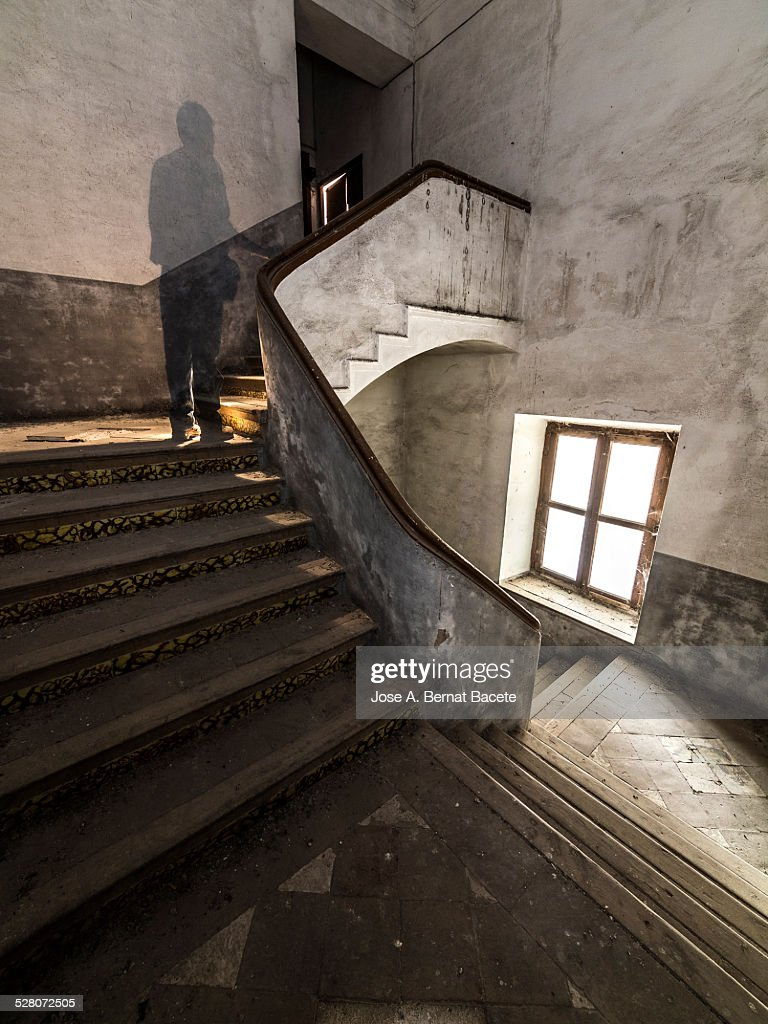 Ancient spiral stairs with a human shade