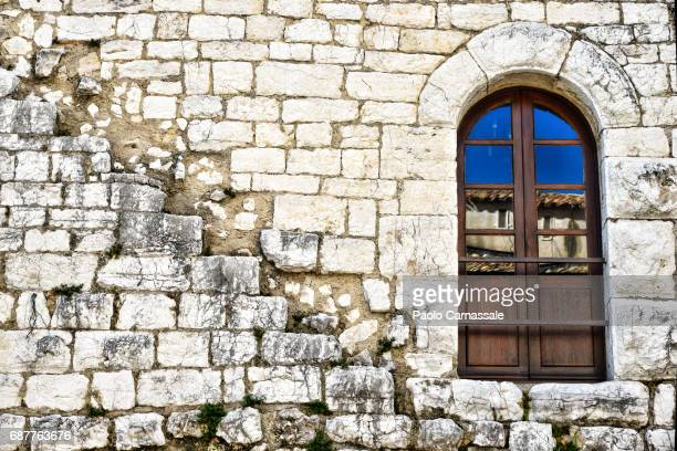 Ancient wall and window with house reflection in Vence, France