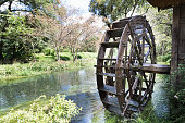 Ancient water wheel within serene and scenic river setting
