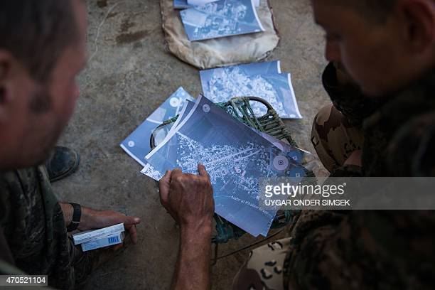 A 40 and a 21 year old from the UK nicknamed by Kurdish fighters as Hewal Cudi and Hewal Sores check maps on April 18 in the outskirts of the...