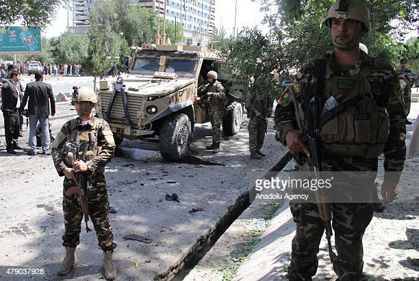 US and Afghan solders inspect the site of a suicide bomb blast that targeted the convoy of foreign troops in Kabul Afghanistan on June 30 2015 A...