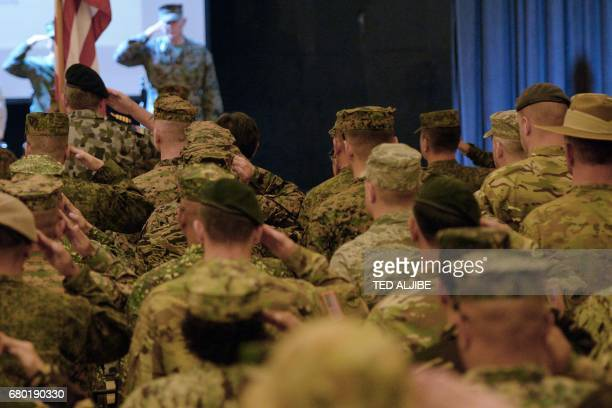 US and Australian soldiers salute in front of a US flag during the opening of the annual PhilippinesUS military exercise at Camp Aguinaldo Quezon...