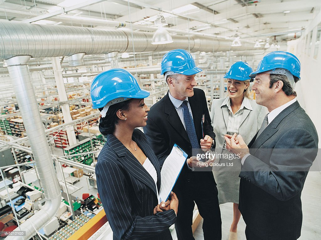 CEO and Business People Wearing Hardhats and Talking in a Factory
