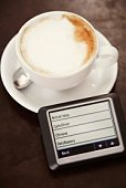 GPS and cup of cappuccino