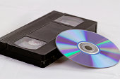 VHS video tape and DVD disk (analog digital) on white background