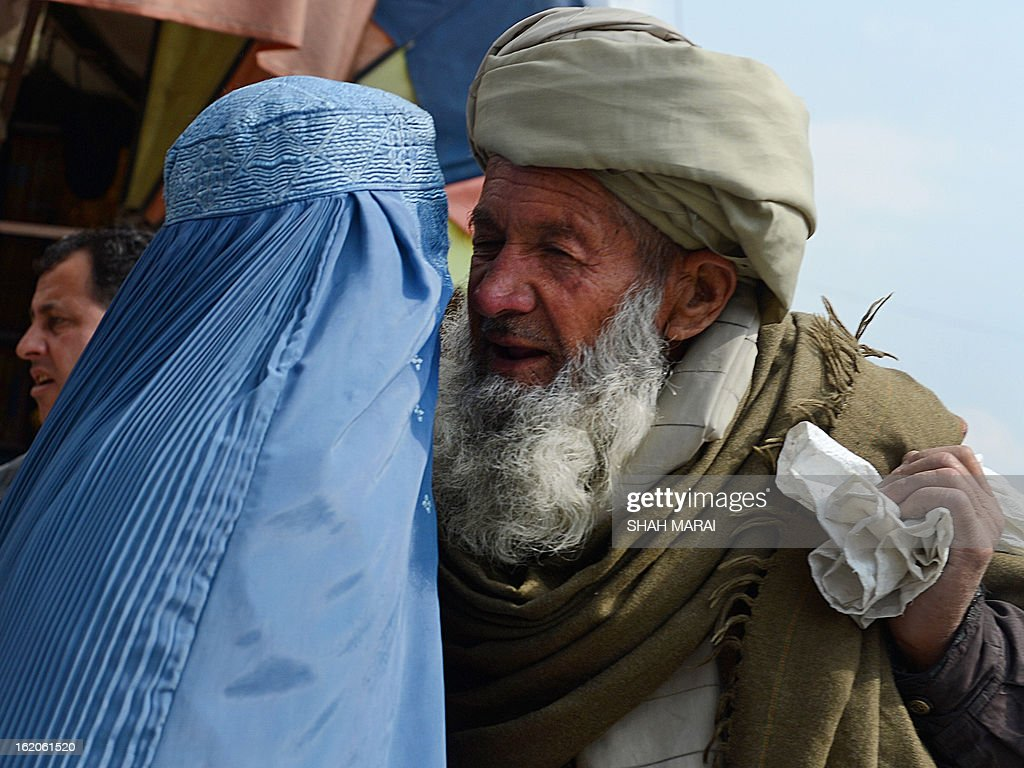 And elderly Afghan man talks to a burqa-clad Afghan woman in Kabul on February 19, 2013. Insurgent attacks on Afghan government employees soared by 700 percent last year even as the overall 2012 civilian death toll from the war fell for the first time in six years, the UN said on February 19. Targeted killings of women in government service by Taliban-led insurgents were 'particularly disturbing', the UN mission in Afghanistan said in its annual report on civilian casualties. AFP PHOTO/ SHAH Marai