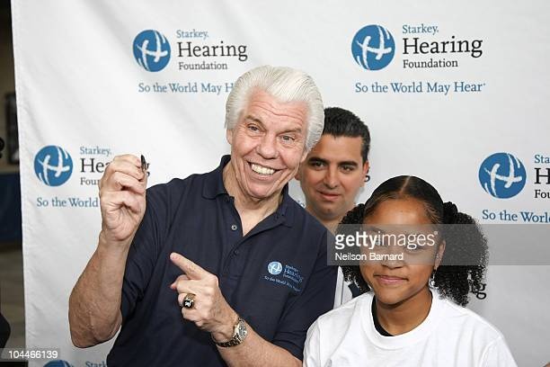 CEO and founder of the Starkey Foundation Bill Austin and Buddy Valastro demonstrate the fitment of an hearing aid during The Starkey Hearing...