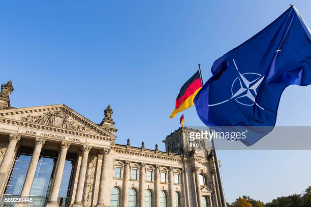 NATO- and german flag with famous inscription on the architrave on the west portal of the Reichstag building in Berlin: 'Dem Deutschen Volke' (Berlin, Germany)