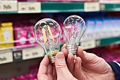 LED and incandescent lamp in the hands of the buyer in the store