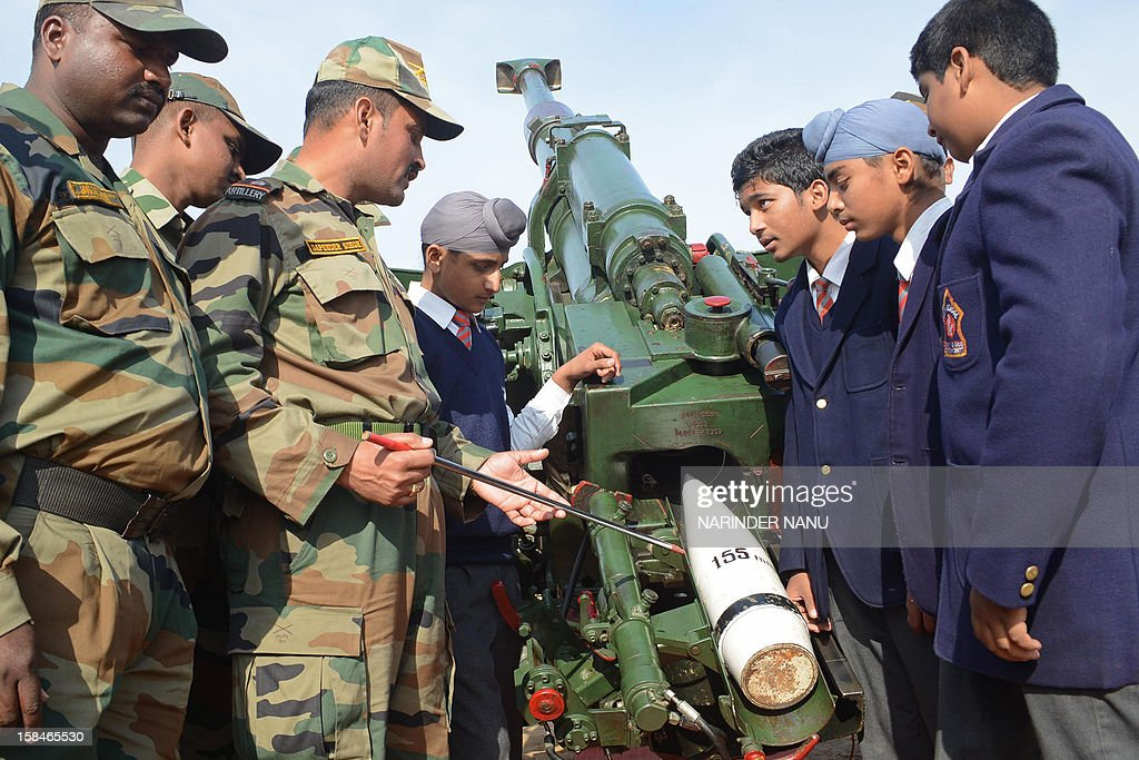 And Indian army officers and schoolchildren pose next to a 155/45 Soltam gun during an Army Mela (fair) and exhibition at Khasa, some 15 kms from Amritsar, on December 17, 2012. The Army Mela (fair ), organised by the Vajra Corps, displayed weapons, tanks, aircraft and military equipment to students and civilian visitors of the event.