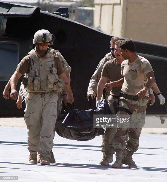 S and Iraqi Army soldiers carry the body of an Iraqi commando killed in a roadside bomb that hit his vehicle September 13 2005 in Tall Afar 260 miles...