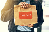 Closeup shot of an unidentifiable delivery man holding a restaurant takeaway