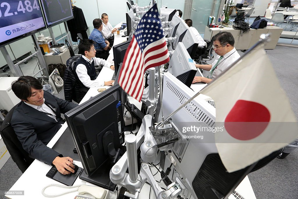 U.S. and Japanese national flags sit on display while dealers work at a foreign exchange brokerage in Tokyo, Japan, on Thursday, Jan. 30, 2014. Japanese stocks fell, with the Topix index closing at its lowest in six weeks, after the yen gained as the Federal Reserve pushed ahead with stimulus cuts amid turmoil in emerging markets. Photographer: Yuriko Nakao/Bloomberg via Getty Images