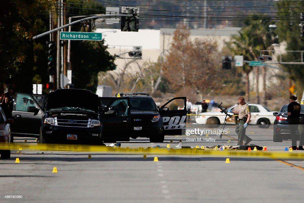 FBI and local law enforcement move a weapon and compile evidence at the scene where suspects of the shooting at the Inland Regional Center were...