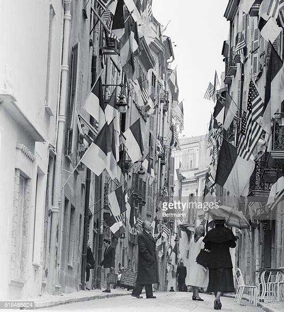 US and Monaco flags fly by the score from buildings along a narrow street in the principality of Prince Rainier III Practically every doorway and...