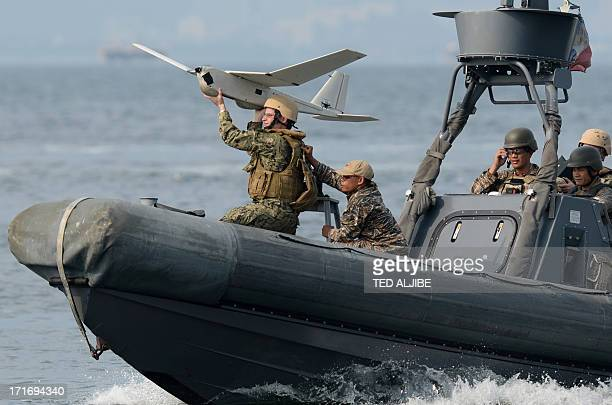 US and Philippine navy personnel prepare to launch unmanned aerial vehicle from a speed boat off the naval base in Sangley point Cavite City west of...