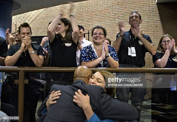 NASA and project staff react with others as telemetry is received from the New Horizons probe at the Johns Hopkins University Applied Physics...