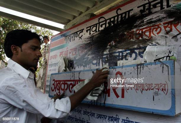 MNS and Samajwadi Party Clashes Violence MNS WORKER CLEANS PARTY'S BOARD WHICH WAS BLACKENED BY SP WORKER AT BANDRA ON MONDAY