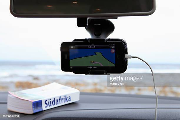 A GPS and South African guidebook on car dashboard