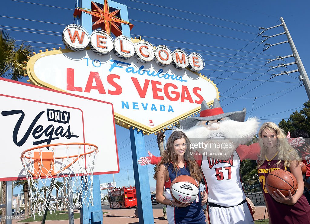 LVCVA and Sports Illustrated Models Natasha Barnard (L) and Genevieve Morton (R) support the NCAA Basketball Conference Championship at the historic Las Vegas sign on February 14, 2013 in Las Vegas, Nevada.