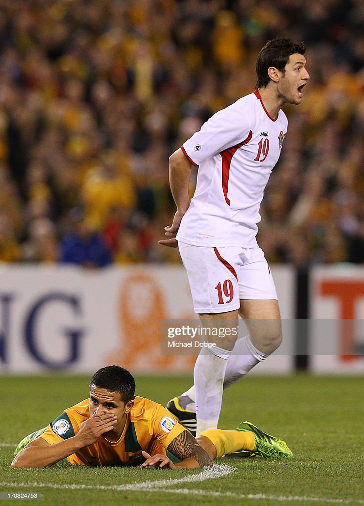 and Tim Cahill of the Socceroos reacts after a contest against Anas Bani Yaseen of Jordan during the FIFA World Cup Qualifier match between the Australian Socceroos and Jordan at Etihad Stadium on June 11, 2013 in Melbourne, Australia.