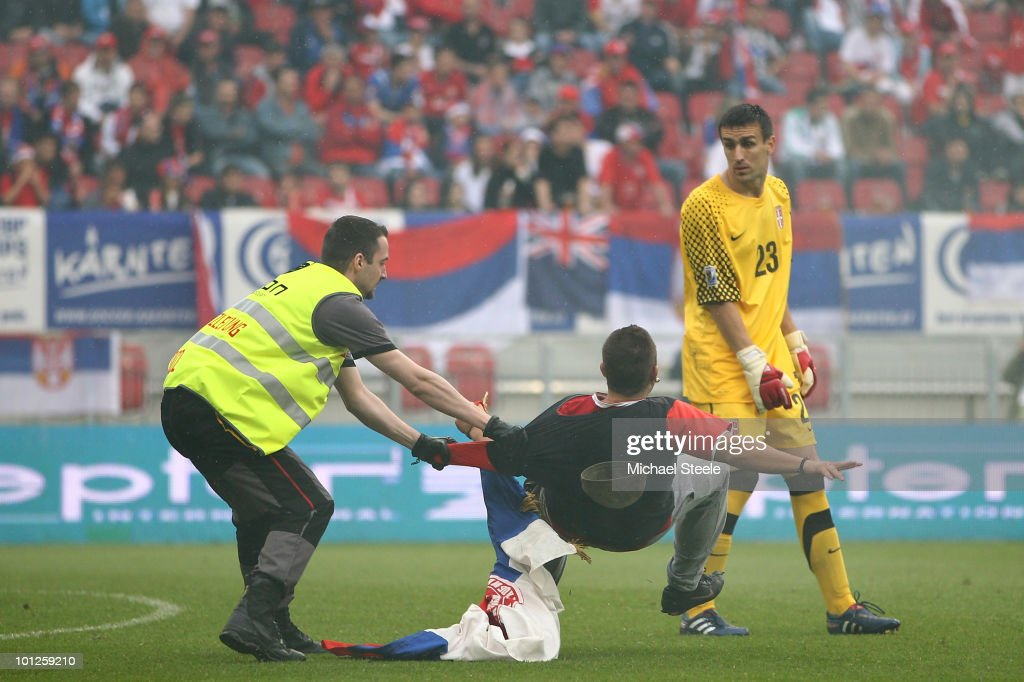 Andelko Duricic (r) the Serbia goalkeeper looks back as a Serbia supporter is pulled to the ground by a security officer during the New Zealand v Serbia International Friendly match at the Hypo Group Arena on May 29, 2010 in Klagenfurt, Austria.