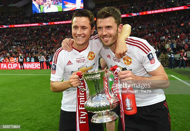 Ander Herrera and Michael Carrick of Manchester United pose for photographs with the FA Cup Trophy after The Emirates FA Cup Final match between...