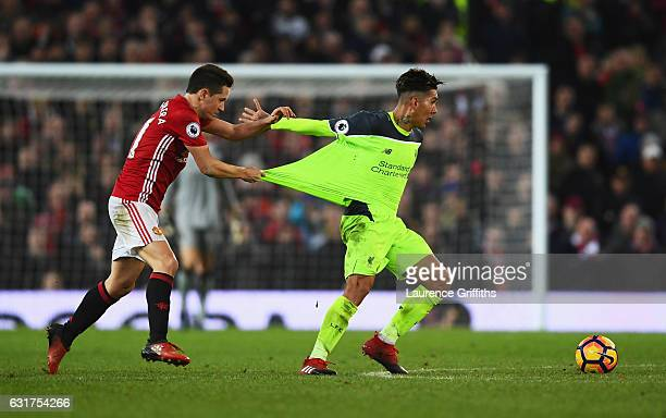 Ander Herrera of Manchester United pulls the shirt of Roberto Firmino of Liverpool as they battle for the ball during the Premier League match...
