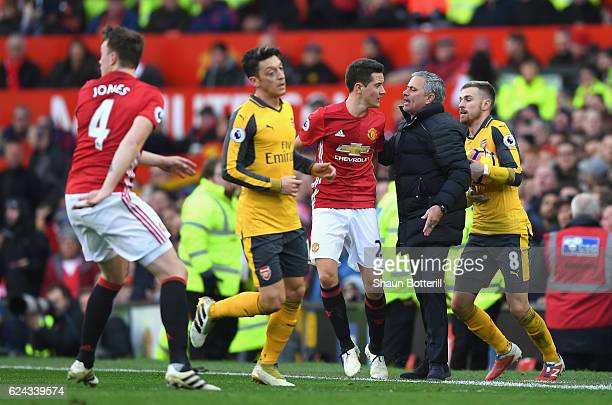 Ander Herrera of Manchester United speaks to Jose Mourinho Manager of Manchester United while Aaron Ramsey of Arsenal attempts to get back onto the...