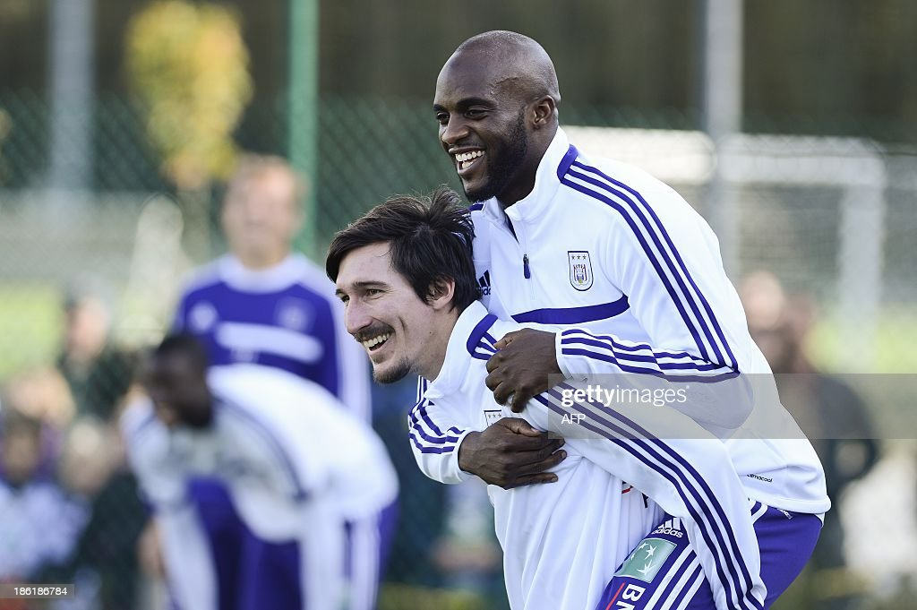 Anderlecht's American mifielder Sacha Kljestan (L) carries Franco-Malian footballer Mohamed Sissoko on his back during an open training session of Belgian First Division football team RSC Anderlecht on October 29, 2013, in Brussels. Sissoko is training with Anderlecht for the first time to decide if he wants to join the club.