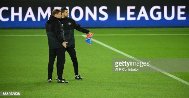 Anderlecht's Belgian head coach Hein Vanhaezebrouck speaks with an assistant during in a training session at the Parc des Princes stadium in Paris on...