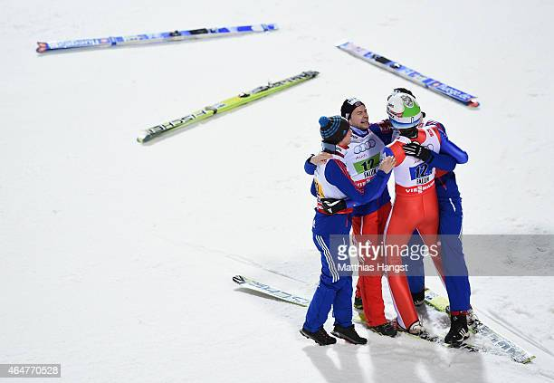 Anders Bardal Anders Jacobsen and Anders Fannemel of Norway congratulate Rune Velta as they win the gold medal in the Men's Team HS134 Large Hill Ski...