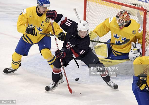Anders Bjoerk of USA Sweden's Andreas Englund and goalkeeper Felix Sandstroem vie during the 2016 IIHF World Junior Ice Hockey Championship bronze...