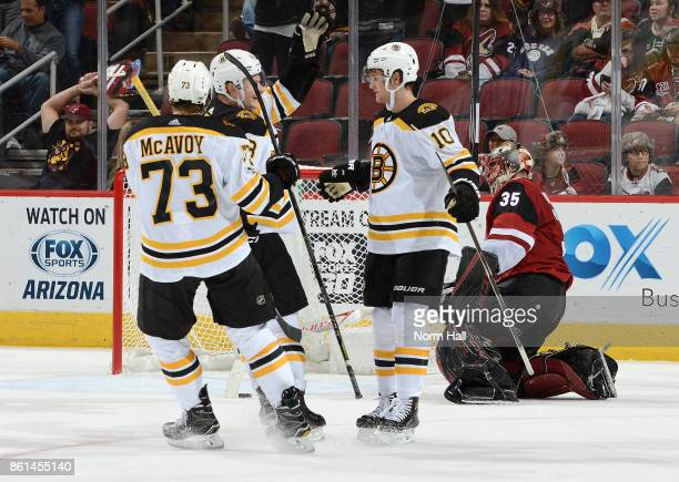 Anders Bjork Charlie McAvoy and Danton Heinen of the Boston Bruins celebrate a third period goal against Louis Domingue of the Arizona Coyotes at...