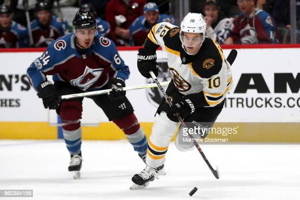 Anders Bjork of the Boston Bruins advances the puck against Nail Yakupov of the Colorado Avalanche at the Pepsi Center on October 11 2017 in Denver...