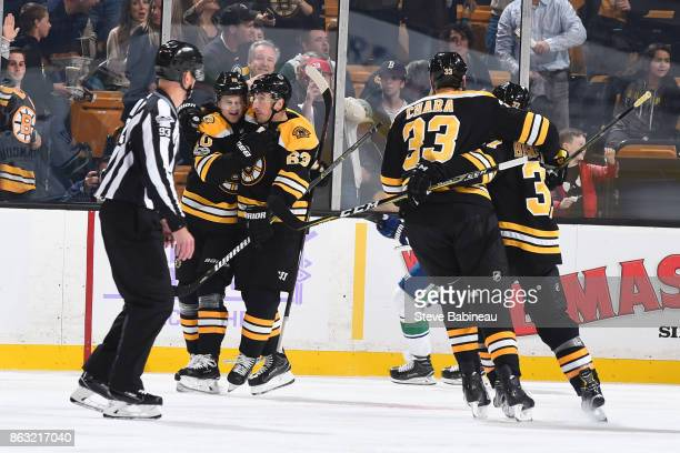 Anders Bjork of the Boston Bruins celebrates a goal with his line mates in the first period against the Vancouver Canucks at the TD Garden on October...