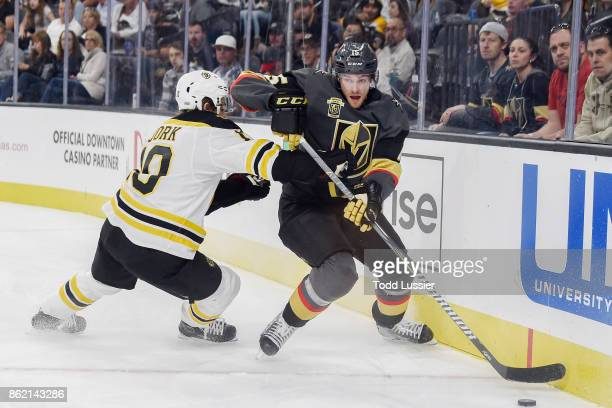 Anders Bjork of the Boston Bruins defends Jon Merrill of the Vegas Golden Knights during the game at TMobile Arena on October 15 2017 in Las Vegas...